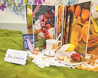 """Sue Lambert ties in a display of a teacup, scone, fruit and teabags for tea time with the book """"Afternoon Tea"""" in the Altered Book Art Gallery."""