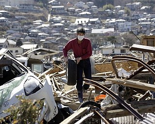 A survivor Keichi Kudo picks up car tire near the his damaged house at a devastated area in Ofunato, Iwate Prefecture, Japan, Wednesday, April 6, 2011, following the March 11 earthquake and tsunami.
