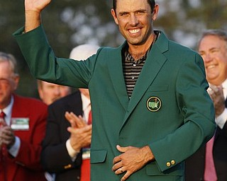 Charl Schwartzel of South Africa waves with his green jacket after winning the Masters championship golf tournament Sunday, April 10, 2011, in Augusta, Ga.