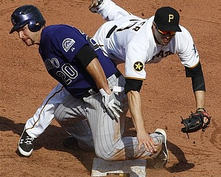Colorado Rockies' Chris Iannetta (20) takes Pittsburgh Pirates second baseman Neil Walker out of the double play after being forced out at second on a seventh inning fielder's choice by Rockies' Ryan Spilborghs during a baseball game in Pittsburgh, Sunday, April 10, 2011. The Rockies won 6-5.