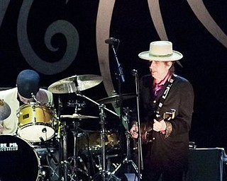 """In this  handout photo released by Saigon Sound System,  US musician Bob Dylan , right,  performs with his band in Ho Chi Minh City, Vietnam Sunday, April 10,  2011. After nearly five decades of singing about a war that continues to haunt a generation of Americans, legendary performer Bob Dylan finally got his chance to see Vietnam at peace.   Dylan, 69, jammed on stage in a black jacket, purple shirt and white hat in the warm evening air, singing favorites such as """"A Hard Rain's a-Gonna Fall"""" and """"Highway 61 Revisited."""""""