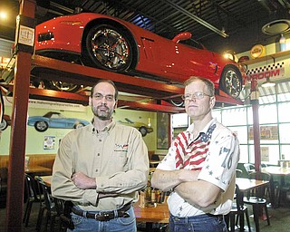 Dave Millich, left, president of the Mahoning Valley Corvettes club, stands near his 2010 Corvette Grand Sport on display at Quaker Steak & Lube in Austintown. His 1984 Fitch High School classmate Rob Bowman, right, has a 1967 Chevy Chevelle on display at the restaurant.