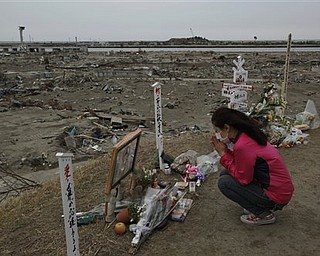 A survivor pray in an area destroyed by tsunami in Natori, Miyagi Prefecture, northern Japan, Monday, April 11, 2011, one month to the day after an earthquake and tsunami devastated the city.