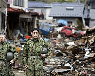 Members of Japanese Self-Defense Force stop for a moment of silence at 2:46pm, exactly a month after a massive earthquake struck the area in the port town of Kesennuma, Miyagi Prefecture, Japan, Monday, April 11, 2011.