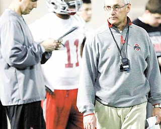 Ohio State head coach Jim Tressel, right, walks away as assistant head coach Luke Fickell, left, looks over a list of plays during the first day of spring NCAA college football practice Thursday, March 31, 2011, in Columbus, Ohio.