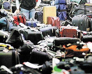 In this Feb. 20, 2007 file photo, Carolann Manfredi, of Princeton, N.J., searches through luggage for a bag she says has been missing for five days, at the Philadelphia International Airport. The Department of Transportation is proposing a new rule, in 2011, requiring automatic refunds for delayed luggage. The major airlines, which are collecting more than $3.3 billion in bag fees a year, are opposed. (AP Photo/Matt Rourke, file)