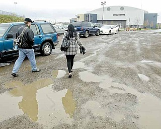 Dave Goettsch and Makeda Mosley, who both work for VXI Global Solutions, try not to get muddy as they walk to work from a free parking lot at the Covelli Centre in downtown Youngstown.