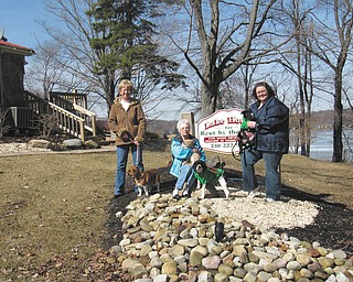 Standing outside The Lake House, from left, are Lora Herbert with Dancer, Sally Geary with Marble and Darby, and HSCC Shelter Manager Heather Jurina with Mel.