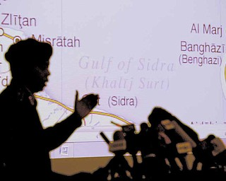 Libyan Army Maj. Gen. Saleh Abdullah Ibrahim gestures during a press conference in Tripoli, Libya, Saturday, April 16, 2011. In the background is a map of Libyan Eastern coastal areas  involved in the fighting.