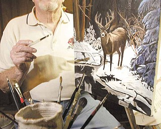 Robert J. Rider Sr. of Austintown, self-taught artist and Korean War-era veteran, sits in his basement-corner studio with one of his paintings showing his favorite subject — the outdoors.