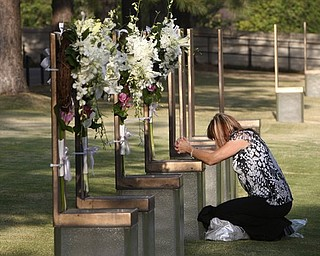 Regina Bonny, a retired Midwest City, Okla., police officer from Moore, Okla., kneels at the chair of DEA agent Kenneth Glenn McCullough in the field of chairs at the Oklahoma City National Memorial and Museum in Oklahoma City, Tuesday, April 19, 2011, on the 16th anniversary of the Oklahoma City bombing.