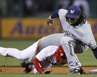 Philadelphia Phillies' Carlos Ruiz rolls under Milwaukee Brewers second baseman Rickie Weeks during the fourth inning of a baseball game Tuesday, April 19, 2011, in Philadelphia. Ruiz was out at second on a ball hit by Wilson Valdez.