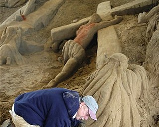 """Artist Roger Powell brushes sand while constructing his 12th annual Easter sand sculpture """"Walking on Common Ground"""" at the Hancock County Fairgrounds in Findlay, Ohio, Tuesday, April 19, 2011. The sculpture uses about 300 tons of sand and is expected to be completed on Good Friday."""