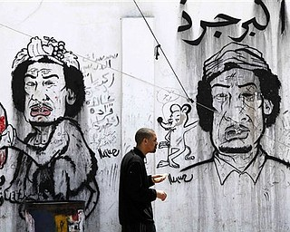 """A man passes graffiti caricatures related to Moammar Gadhafi and Brega, during a funeral in Benghazi, Tuesday, April 19, 2011. The writing on the wall reads """"the greatest rat of all,"""" in Arabic. Europe is ready to send an armed force to Libya to ensure delivery of humanitarian aid and Britain said Tuesday it will dispatch senior military officers to advise the opposition  - signs that Western nations are inching closer to having troops on Libyan soil."""