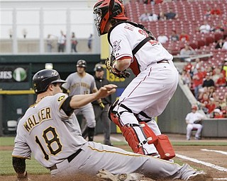 Pittsburgh Pirates' Neil Walker (18) scores as Cincinnati Reds catcher Ryan Hanigan waits for the throw in the first inning of a major league baseball game, Monday, April 18, 2011 in Cincinnati. Walker scored on a hit by Chris Snyder.