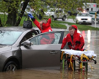 Green Twp. Fire firefighter/paramedic Don Patterson, left, and Lt. Arlis Boggs, right, rescue a woman  from her car, which was stuck in high water on Tuesday, April 19, 2011 in Green Twp., Ohio. Water from a lake behind the houses, combined with with clogged sewer drains caused the water to reach her doors. The woman was uninjured, but rescue personnel used a stretcher to transport her to dry ground.