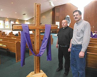 The Rev. Stephen Popovich, pastor of St. Paul the Apostle Church in New Middletown, and Russ Ohlin, a church member, stand next to the handmade cross and base that Ohlin crafted. The cross, which has been on display during Lent, will be carried in a Good Friday service at 7 p.m. today.
