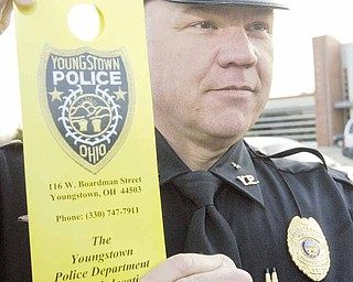 """Lt. William Ross of the Youngstown Police Department shows off one of the door-hangers that were placed on doors on South Side houses in neighborhoods along Market Street on Thursday evening. The back of the door hangers list various notices, such as """"animal complaint"""" or """"loud music complaint,"""" and the police officers will mark which notices apply to a specific residence."""