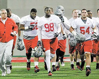 FILE - In this March 31, 2011 file photo, Ohio State defensive coach Jim Haycock, left, runs with a group of defensive players during the first day of NCAA college football practice  in Columbus, Ohio.  Even though most of the starters from a year ago have graduated, one of the biggest surprises at Ohio State this spring is the effectiveness of the Buckeyes defense. (AP Photo/Terry Gilliam)