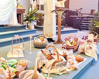 Deacon Nick Moliterno blesses parishioners' Easter baskets, which he says represent the heavenly feast that awaits Christians.