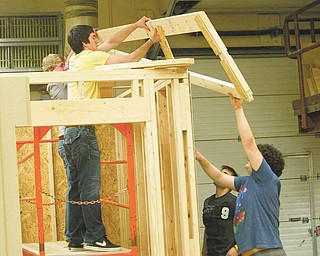 Students in Glenn Sivak's class at Boardman High School take on the task of building a concession stand for the school baseball field. From the bottom in black are seniors Dustin Ronci and Dominic DiCioccio. On top are juniors Tyler Mobley and Tom Haus.