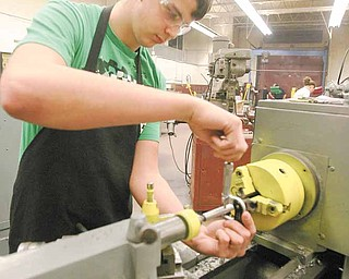 Boardman sophomore Scott Glenn works on a machine lathe as he measures a handle for the vise he is constructing.