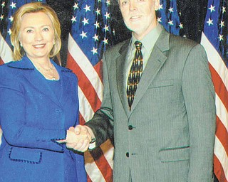 Secretary of State Hillary Clinton greets Ron Elkins, a Poland native who retired and returned to the Mahoning Valley after 23 years as a foreign service officer. Clinton was Elkins'  former boss.