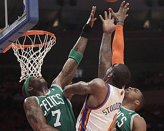 Boston Celtics center Jermaine O'Neal (7) and forward Glen Davis, right, go up for a rebound with New York Knicks forward Amare Stoudemire (1) in the first half of Game 4 of a first-round NBA basketball playoff series at Madison Square Garden in New York, Sunday, April 24, 2011.