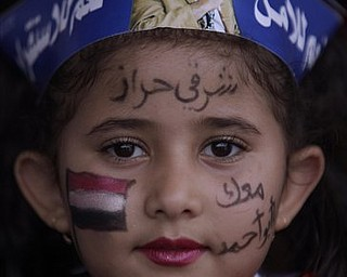 """A Yemeni girl looks on during a rally supporting President Ali Abdullah Saleh, in Sanaa,Yemen, Friday, April 22, 2011.  Opponents and supporters of Yemen's embattled president are marching in cities and towns across the nation for rival rallies after Friday prayers. Arabic reads on her face, """" We are with you""""."""