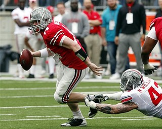 Ohio State quarterback Joe Bauserman (14) breaks a tackle by defensive lineman Nathan Williams (43)during an NCAA college football Spring Game Saturday, April 23, 2011, in Columbus, Ohio.