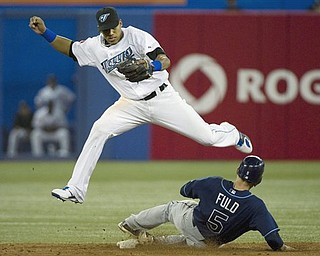 Toronto Blue Jays shortstop Yunel Escobar, top, forces out Tampa Bay Rays left fielder Sam Fuld, bottom on a single hit by Rays DH Johnny Damon, not shown during seveth inning AL Baseball action in Toronto on Saturday, April 23, 2011.