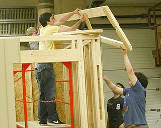 ROBERT K. YOSAY | THE VINDICATOR..Taking on the task of completely building a concession stand from design to ordering supplies then building the stand for the High School Baseball field  students in Mr. Glenn Sivak's  work class - from the bottom in black Dustin Ronci (sr) Dominic DiCioccio (sr) - on top is  Tyler Mobley (jr) (yellow) and  Tom Haus (jr) (gray)  - as they put the first of the roof trusses in place -..-30-