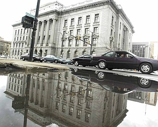 The county courthouse in downtown Youngstown is reflected in standing water Monday after more than a week of rain.