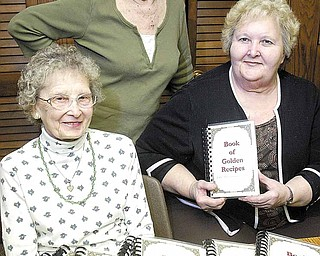 "Pat Gergel stands with Olga Brown, left, president of St. Anne's Guild, and Carol Kaszowski, guild vice president. They have been involved with the publication of the 100th Anniversary Edition of ""Book of Golden Recipes,"" marking the anniversary of Holy Trinity Ukrainian Catholic Church of Youngstown."