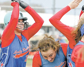 Western Reserve's Sissy Stubbs, left, gets high fives from teammates after hitting a home run during Tuesday's Inter Tri-County League softball game against Jackson-Milton. Western Reserve's Rachael Obradovich, center, avoids the celebration.