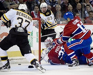 Montreal Canadiens' goaltender Carey Price, bottom, is scored on by Boston Bruins' Patrice Bergeron (37) as Canadiens' Scott Gomez (11) and Bruins' Brad Marchand (63) look for a rebound during second period of Game 4 of a first-round NHL Stanley Cup playoff series in Montreal, Thursday, April 21, 2011.