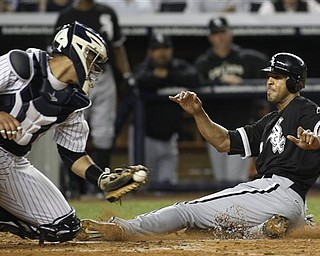 New York Yankees catcher Gustavo Molina looks to make the tag as Chicago White Sox's Alex Rios scores in the fifth inning of a baseball game at Yankee Stadium on Tuesday, April 26, 2011, in New York.