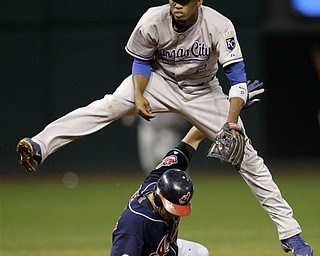 Kansas City Royals shortstop Alcides Escobar leaps over Cleveland Indians baserunner Shin-Soo Choo after forcing him out at second and then throwing to first on a ground ball by Indians' batter Carlos Santana in the fifth inning of a baseball game in Cleveland on Tuesday, April 26, 2011.  Santana was safe at first on the play.
