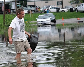 John Brisentine walks through water nearly up to his knees Monday, April 25, 2011 as he carries a tire he found near the submerged intersection of 3rd and Vienna streets in Metropolis, Ill. The Ohio River is threatening homes in that part of the city.