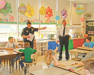 """The right way: During a """"Safety On Wheels"""" program presented by Hubbard Optimist Club on April 15 at St. Patrick School in Hubbard, from left, Lou Carsone, acting Hubbard City Police Chief, and Todd Coonce, Hubbard Township Police Chief, taught second-grade students proper hand signals to use while riding their bikes on roadways. During the bike safety program the students also learned that if a city or township police officer sees them wearing a helmet while riding a bike, they will receive a certificate for a free treat from Hubbard Dairy Queen. Following the bike safety program the Optimist Club gave each student a new bike helmet."""