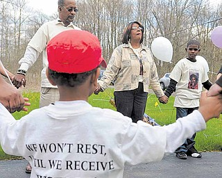 Elder Rose Carter, center, leads family and friends of Vivian Martin in prayer at the Nelson Avenue house where Martin was murdered.