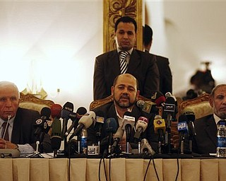 Chief Fatah negotiator for the reconciliation talks Azzam al-Ahmed, left, sits next to Hamas leaders Moussa Abu Marzoug, center, and Mahmoud Al Zahar, right, during a news conference in Cairo, Egypt, Wednesday, April 27, 2011. Palestinians have reached initial agreement on reuniting their rival governments in the West Bank and Gaza, officials from both sides said Wednesday, a step that would remove a main obstacle in the way of peace efforts with Israel. (AP Photo/Khalil Hamra)