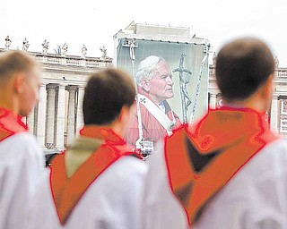 A Polish choir sings in front of a giant photograph of late Pope John Paul II, set up in St. Peter's Square, at the Vatican, Saturday, April 30, 2011. On Sunday, Pope Benedict XVI will beatify John Paul II in St. Peter's Square at the Vatican.