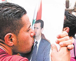 A Syrian pro-government supporter kisses a picture of Syrian President Bashar Assad during a protest to show support to the Syrian regime in old Damascus, Syria, Saturday, April 30, 2011, pictured on a government-provided tour. Syrian army troops backed by tanks and helicopters on Saturday took a prominent mosque that had been controlled by residents in a besieged southern city, killing four people, a witness said.