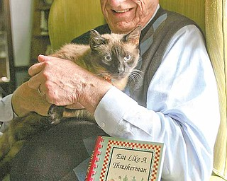 """Hugh Earnhart holds his cat Boxcar Willie next to their cookbook """"Eat Like a Thresherman,"""" a compilation of recipes from Earnhart's grandmother. Willie """"helped"""" Earnhart, a retired Youngstown State University professor, write the book."""