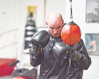 """Former middleweight boxing champion Kelly """"The Ghost"""" Pavlik concentrates on a double-ended punching bag during a workout at the Southside Boxing Club in preparation for his upcoming fight next weekend."""