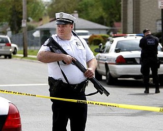 A Columbus police officer stands guard near the scene of a shooting in Columbus, Ohio on Saturday, April 30, 2011.   Authorities have identified the man killed in a shootout with police that left four people injured, including three officers. Columbus police identified him as 27-year-old Randle Lee Roberts II. They didn't say where he lives.  They learned after the shootout Saturday that Roberts might be a suspect in a quadruple homicide about 90 miles south in Adams County at a house along a rural state highway near the village of West Union.  An Adams County dispatcher confirms the sheriff's office is investigating the four deaths but hasn't released details.