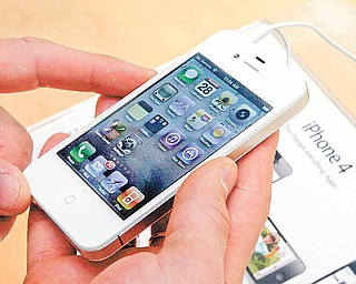 In this April 28, 2011 photo, a customer holds a white iPhone at the Apple store on New York's Upper West Side. People are turning over personal information to online retailers, social networks and others in growing numbers, even as concerns about privacy mount.
