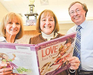 """From left, Seaborn Elementary School library aide Marci Buchanan, Principal Cynthia Mulgrew and her husband, Edward Mulgrew, with a copy of Tim McGraw's book """"Love Your Heart"""" in Mineral Ridge. The book features a character named Mrs. Mulgrew but was not based on the Seaborn principal."""