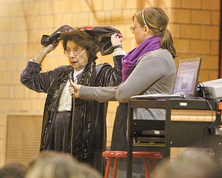 Holocaust survivor Agi Geva, left, shows students how she and her younger sister wore scarves to appear older when they arrived at Auschwitz. Their mother told them older girls were able to work and were spared when the guards divided Jews into separate groups. Next to Geva is Amy Grunenwald, also from the United States Holocaust Memorial Museum.